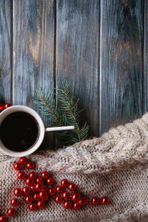 christmas spirit and holidays festivity. decor elements on wooden background. knitted sweater and red bead string with a cup of hot coffee.
