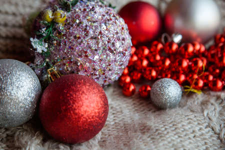 shiny glittery christmas balls selection. red and silver baubles bead string on the knit textured fabric. new year decoration and festive mood concept.