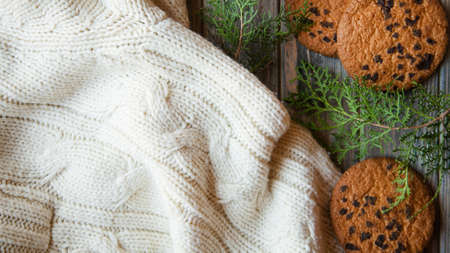 cozy christmas decor. knitted texture blanket chocolate chip cookies and juniper branches background. festive holiday spirit concept.