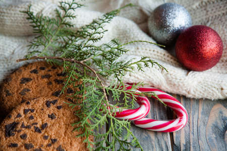 cozy christmas decor. shiny balls on knitted texture blanket chocolate chip cookies stripy candy cane and juniper branches background.