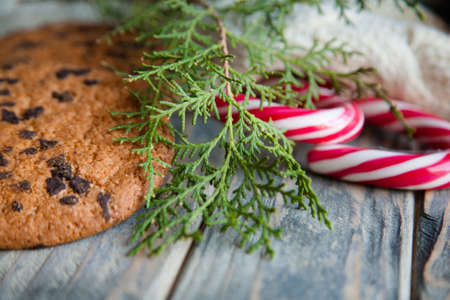 festive new year decor. candy cane chocolate chip cookies and juniper twig on rustic wooden background.