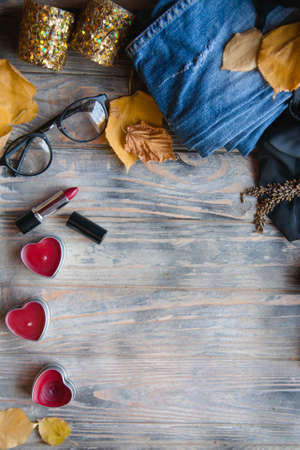 autumnal female lifestyle and makeup. bright red lipstick to fight melancholy. flat lay of heart shape candles, hipster glasses and fallen leaves on wooden background with empty space.