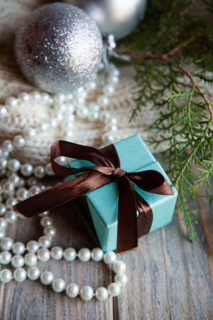 holiday celebration present. blue gift box with chocolate brown ribbon bow juniper twig and pearl beads string on rustic wooden background.