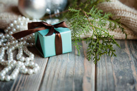 christmas gift on festive holiday background. present blue box and tied with chocolate brown ribbon.