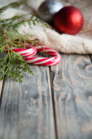 holiday decoration on wooden background. stripy candy cane juniper twig and balls on knitted blanket on rustic texture surface. Stock Photo