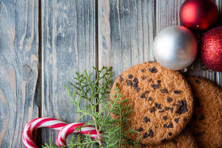 festive christmas decor. balls candy cane chocolate chip cookies and juniper twig on rustic wooden background.