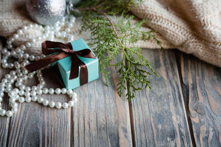 seasonal holiday decor on wooden background. blue gift box with chocolate brown ribbon bow juniper twig and pearl beads string on rustic textured surface. Stock Photo
