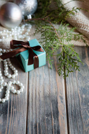 new year gift on festive holiday background. present in blue box and tied with chocolate brown ribbon. Stock Photo
