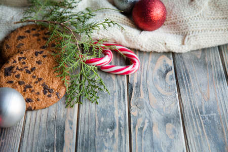 festive holiday decor. shiny balls on knitted texture blanket chocolate chip cookies stripy candy cane and juniper branches on wooden background. Stock Photo