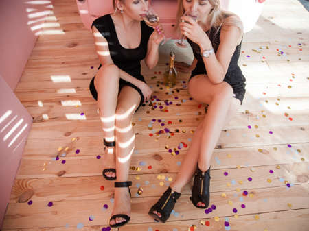 Party for two. Women sitting on floor and drinking wine. Festive floor decoration.