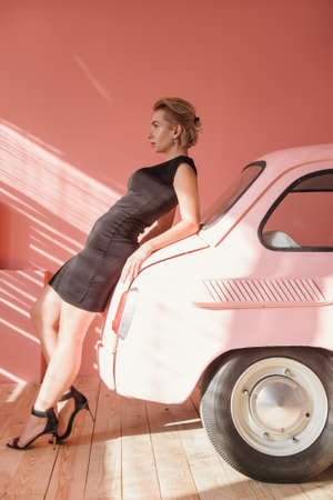 Fashion model leaning on pink car. Young woman looking forward. Vintage style.