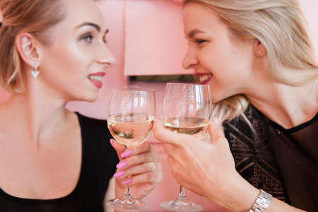Party for two. Blonde women with wine glasses. Female hangout.