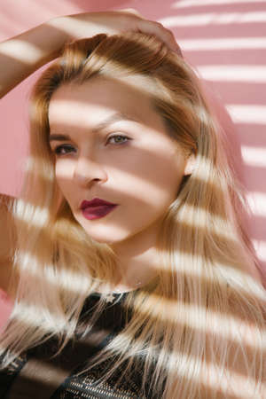 Young blonde woman portrait. Female fashion model. Blinds shadow effect. Stock Photo