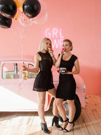 Party for two. Celebrating girls concept. Black and coral red background.