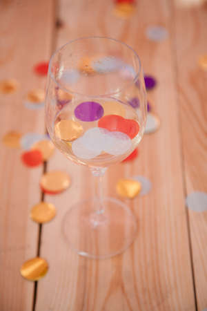 Party over concept. Half empty glass with wine and confetti on wooden background.