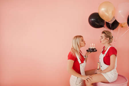 Friendship anniversary. Two girls blowing out candles. Copy space on coral red background. Stock Photo