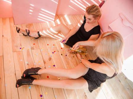 Birthday celebration. Blonde girls sit on wooden floor drink white wine. Festive background.