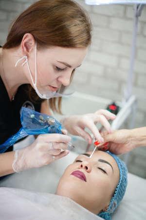 Decorative cosmetology courses. Female beautician using tattoo machine for eyebrow microblading. Фото со стока - 130033774