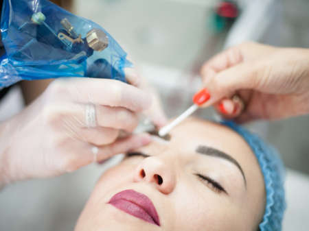 Decorative cosmetology courses. Female beautician using tattoo machine for eyebrow microblading. Фото со стока - 130033776