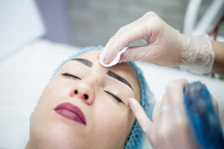 Decorative cosmetology. Eyebrow design. Closeup portrait of female client enjoying beauty procedure. Фото со стока - 130033777