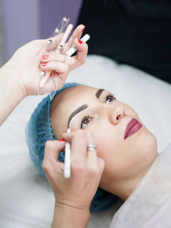 Decorative cosmetology, microblading. Beautician working on eyebrow design in salon.