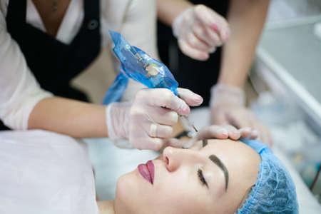 Permanent Make-up-Kurs. Ausgeschnittene Aufnahme einer Kosmetikerin, die einem Praktikanten beibringt, wie man eine Tätowiermaschine für das Microblading der Augenbrauen verwendet. Standard-Bild