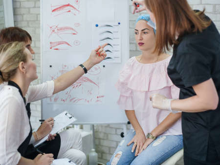 Permanent makeup. Professional courses. Female interns studying eyebrow design and new techniques. Фото со стока - 130033847