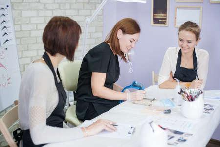 Permanent makeup class. Beautician teaching female interns how to sketch up symmetrical eyebrows. Фото со стока - 130033850