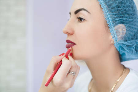 Decorative cosmetology. Permanent makeup. Beautician trying color on lady lips before tattoo procedure. Фото со стока - 130033866