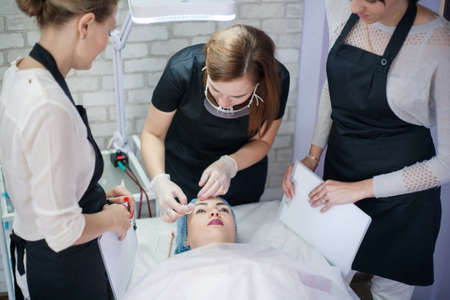 Professional skin care therapy. Female beauticians working with client in modern clinic.