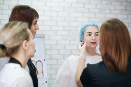 Decorative cosmetology. Female beauticians examining lady face before skin care procedure. Фото со стока - 130033893