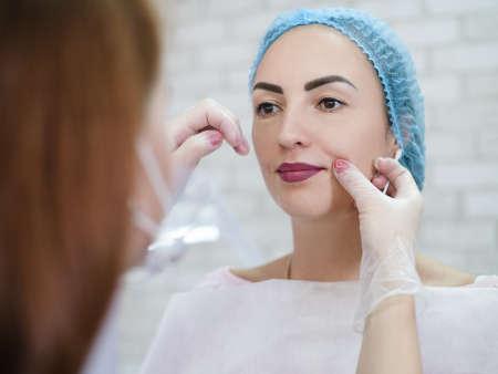 Decorative cosmetology. Permanent lip makeup. Female beautician examining lady face. Фото со стока - 130033894