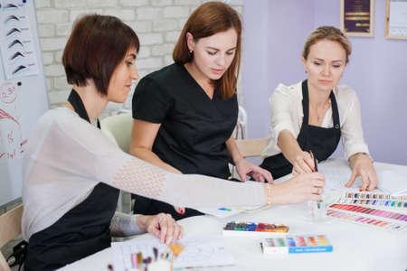 cours théorique de cosmétologie décorative. Mesdames étudiant les couleurs, utilisant la palette, la peinture et les pinceaux.