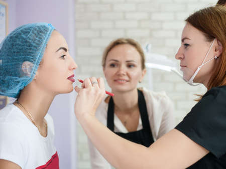 Permanent makeup course. Female beautician trying color on lady lips before tattoo procedure. Фото со стока - 130033901
