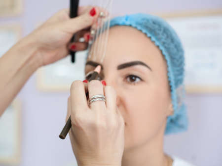 Permanent makeup. Professional female artist measuring eyebrow to create perfect design.
