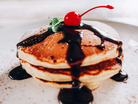 Professional catering service. American pancakes. Crepe pile with chocolate topping cherry.
