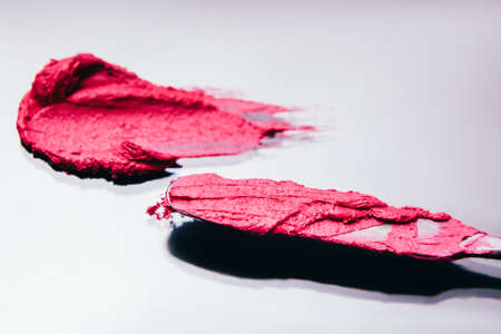 Makeup art. Decorative cosmetics. Pink lipstick stroke made with spatula on white background.
