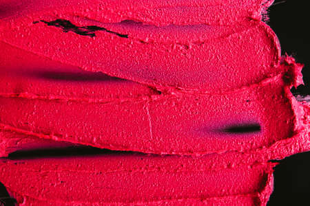 Smudged lipstick. Makeup artistry beauty. Crimson red textured strokes on dark background.