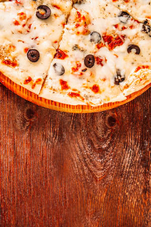 Culinary master class. Italian cuisine. Sliced pizza on brown rustic wooden background.