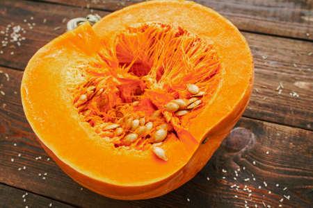 Healthy diet. Fall seasonal organic fruit. Orange pumpkin half on wooden table.