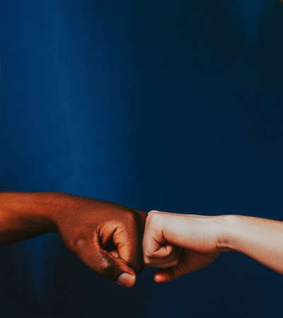 Racial tolerance. Respect social unity. Fist bump gesture. African Caucasian people hands.