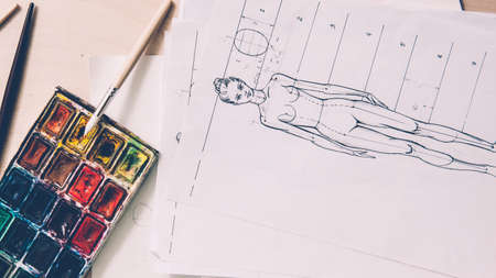 Designer workplace. Fashion sketching. Female model drawing. Paint palette brush on table. Zdjęcie Seryjne