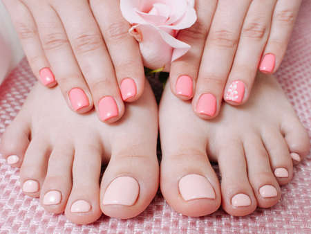 Nail care service. Skin therapy. Manicure pedicure. Female hands feet. Pastel peach polish.