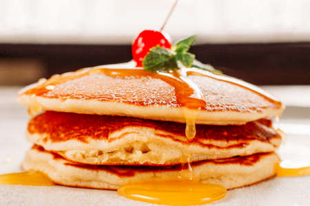 American cuisine. Homemade pancakes. Crepe stack with honey topping mint leaf cherry.