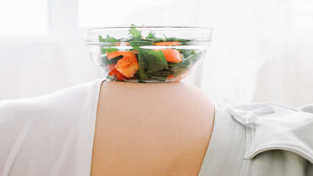 Healthy eating. Vegetarian diet. Fresh salad bowl on pregnant woman belly.