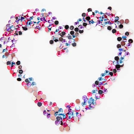 Romantic background. Valentine greeting. Multicolor rhinestone heart shape frame on white. Zdjęcie Seryjne