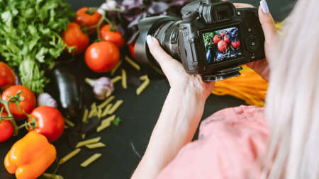 Food blog. Cookbook recipe. Female photographer taking picture of organic vegetables.