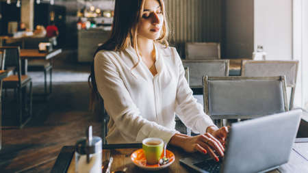Freelancer lifestyle. Online job. Relaxed business woman working on laptop in coffee shop.