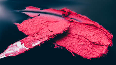 Makeup school. Artistry business. Crimson red lipstick smear made with spatula.