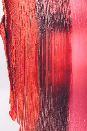 Smudged lipstick. Makeup artistry business. Textured orange pink strokes. Creative background.